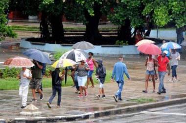 Personas protegiéndose de la lluvia al transitar por el Vedado, en La Habana. Foto: Omara García Mederos/ ACN.
